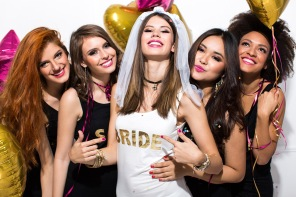 Young girlfriends celebrating bride night. Bride is wearing a veil and a T-shirt with the inscription ''BRIDE'', bridesmaids are wearing T-shirt with the inscription ''Squad''. Thez are laughing, dancing and singing. Room is decorated with star and heart shaped balloons.